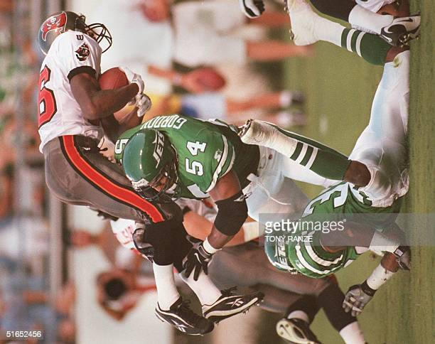 Tampa Bay Buccaneers wide receiver Karl Williams is upended by New York Jets defensive line backer Dwayne Gordon and corner back Raymond Austin...