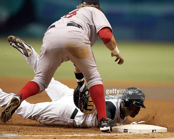 Tampa Bay Devil Rays left fielder Carl Crawford dives back to first on a pickoff attempt from Boston's Curt Schilling as Kevin Millar applies the tag...