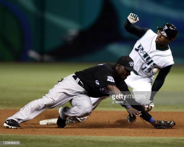 Tampa Bay Devil Rays outfielder Carl Crawford slides safely into second base with a steal as Toronto Blue Jays infielder Orlando Hudson tries to make...