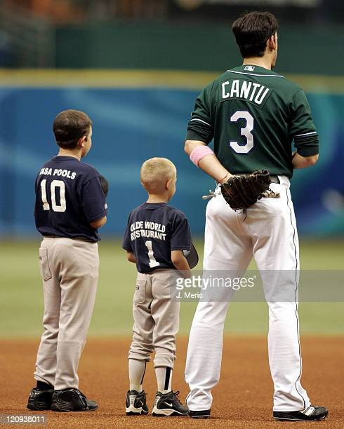 Tampa Bay Devil Rays third baseman Jorge Cantu sings the national anthem along with some little leaguers prior to Sunday's game against the Minnesota...