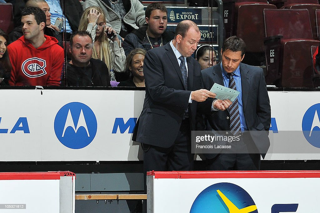 Tampa Bay Head Coach Guy Boucher discuss strategy with assistant Dan Lacroix before the NHL game against the MOntreal Canadiens fon October 13, 2010 at the Bell Centre in Montreal, Quebec, Canada.