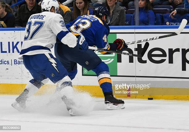 Tampa Bay Lightning center Yanni Gourde and St Louis Blues defenseman Jordan Schmaltz compete for the puck on the boards during a NHL game between...