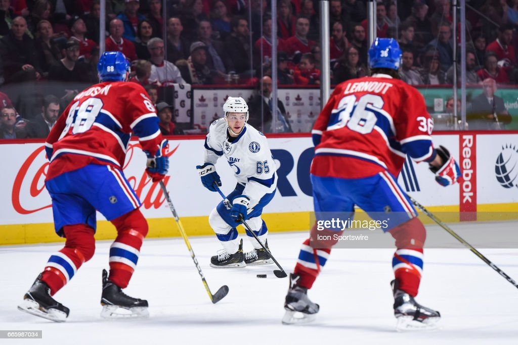 Tampa Bay Lightning Center Yanni Gourde (65) controlling the puck facing Montreal Canadiens Defenceman Brandon Davidson (88) and Montreal Canadiens Defenceman Brett Lernout (36) in defense during the Tampa Bay Lightning versus the Montreal Canadiens game on April 7, 2017, at Bell Centre in Montreal, QC