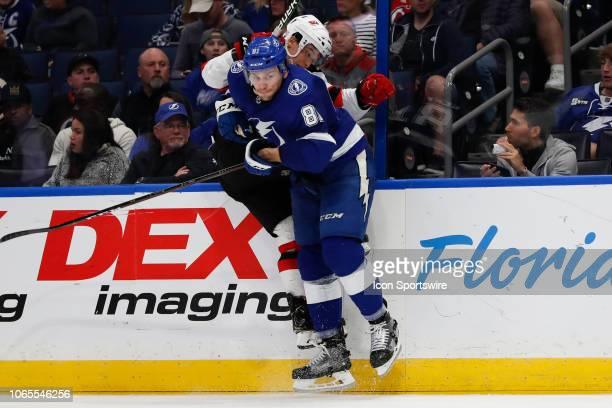 Tampa Bay Lightning defenseman Erik Cernak checks New Jersey Devils left wing Brett Seney during the regular season NHL game between the New Jersey...