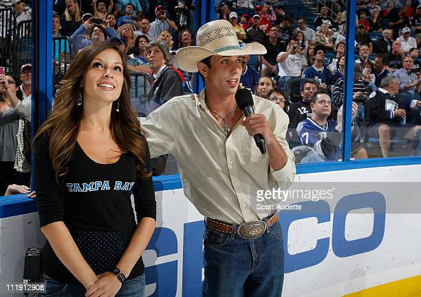 Tampa Bay Lightning ingame host Brittany Zion stands with JB Mauney a Pro Bull Rider who starts the game with saying Let's Play Hockey between the...