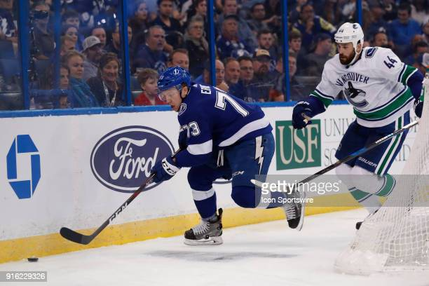 Tampa Bay Lightning left wing Adam Erne skates the puck away from Vancouver Canucks defenseman Erik Gudbranson in the second period of the NHL game...