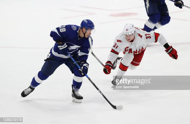 Tampa Bay Lightning left wing Ondrej Palat skates the puck away from Carolina Hurricanes right wing Andrei Svechnikov during Game 3 of the Second...