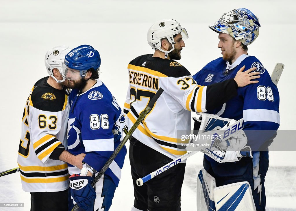 Tampa Bay Lightning right wing Nikita Kucherov (86) and Boston Bruins left wing Brad Marchand (63) shake hands while Boston Bruins center Patrice Bergeron (37) congratulates Tampa Bay Lightning goalie Andrei Vasilevsky (88) after an NHL Stanley Cup Eastern Conference Playoffs game between the Boston Bruins and the Tampa Bay Lightning on May 06, 2018, at Amalie Arena in Tampa, FL. The Lightning defeated the Bruins 3-1 to win the series 4-1.