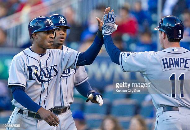 Tampa Bay Rays' BJ Upton left and Carl Crawford are congratulated by Brad Hawpe after both scored on a triple by Matt Joyce in the first inning...