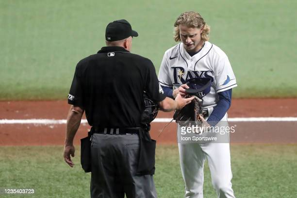Tampa Bay Rays Pitcher Shane Baz has his glove, hat and waist band checked between innings by the home plate umpire during the regular season game...