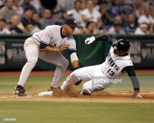 Tampa Bay's Carl Crawford slides safely into third with a triple as New York's Alex Rodriguez is late with the tag in Wednesday night's game at...