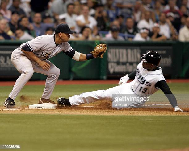 Tampa Bay's Carl Crawford slides safely into third with a triple as New York's Alex Rodriguez prepares for the tag in Wednesday night's game at...