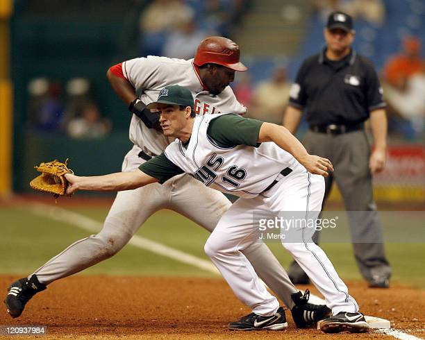 Tampa Bay's Travis Lee makes the grab at first as Angel's outfielder Vladimir Guerrero makes it back safely during Wednesday's action at Tropicana...