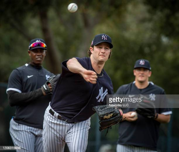 New York Yankees' pitcher Gerrit Cole fielding a hit ball while his teammates watch during spring training in Tampa Florida on February 13 2020