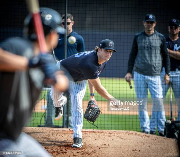 New York Yankees' pitcher Gerrit Cole pitching to batters from the mound with manager Aaron Boone, center and bench coach Carlos Mendoza looking on...