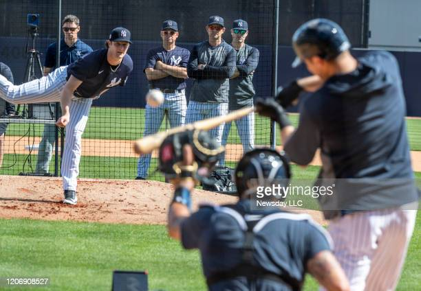 New York Yankees' pitcher Gerrit Cole pitching to batters from the mound with manager Aaron Boone, front center, bench coach Carlos Mendoza, left and...