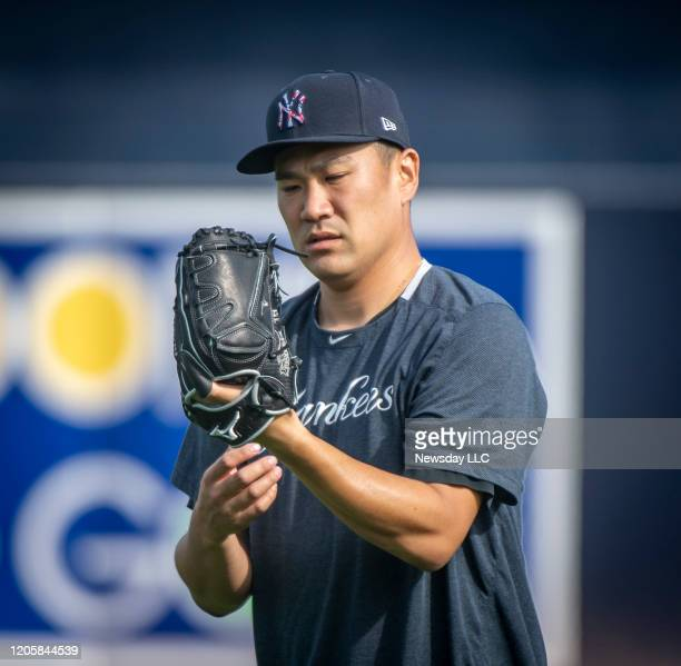 New York Yankees' pitcher Masahiro Tanaka warming up his arm before throwing in the bullpen on the first day of spring training in Tampa Florida on...