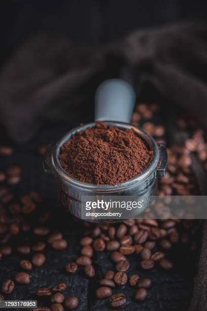 tamped puck of coffee grounds within basket of portafilter and coffee beans - café moulu photos et images de collection