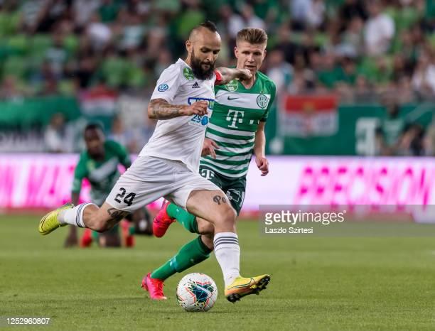 Tamás Cseri of Mezokovesd Zsory FC shoots on goal next to Dávid Sigér of Ferencvarosi TC during the Hungarian OTP Bank Liga match between...