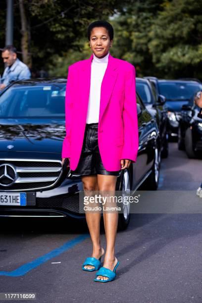Tamu McPherson, wearing a fuchsia blazer, black leather shorts and blue Bottega Veneta sandals, is seen outside the Tod's show during Milan Fashion...
