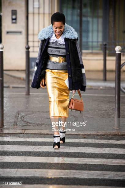 Tamu McPherson wearing a grey jumper gold belt gold midi skirt blue jacket with fur details and black and silver heels is seen outside the Miu Miu...