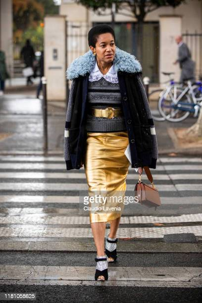 Tamu McPherson, wearing a grey jumper, gold belt, gold midi skirt, blue jacket with fur details and black and silver heels, is seen outside the Miu...