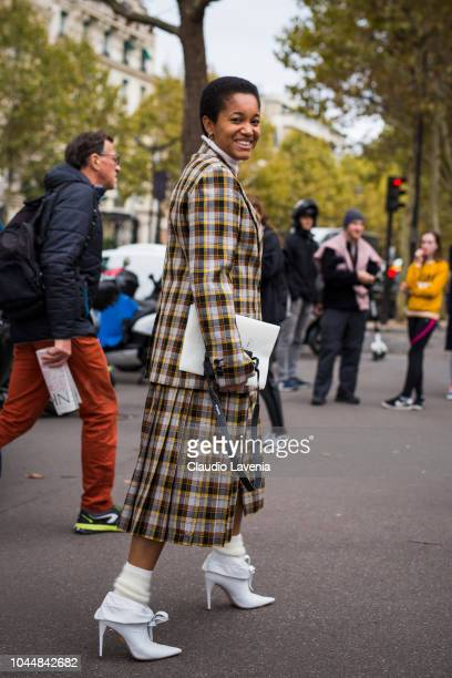 Tamu McPherson wearing a plaid blazer with matching midi skirt and white boots is seen before the Miu Miu show on October 2 2018 in Paris France