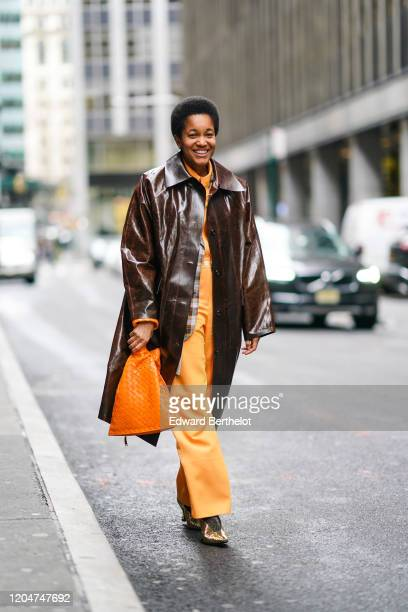 Tamu Mcpherson wears a brown leather shiny long coat, an orange knitted bag, orange flared pants, pointy shoes, outside Cinq a Sept, during New York...