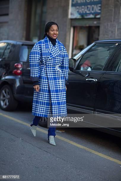 Tamu McPherson wears a light blue plaid coat blue stirup Vetements pants and Altuzarra houndstooth mule shoes during Milan Men's Fashion Week...