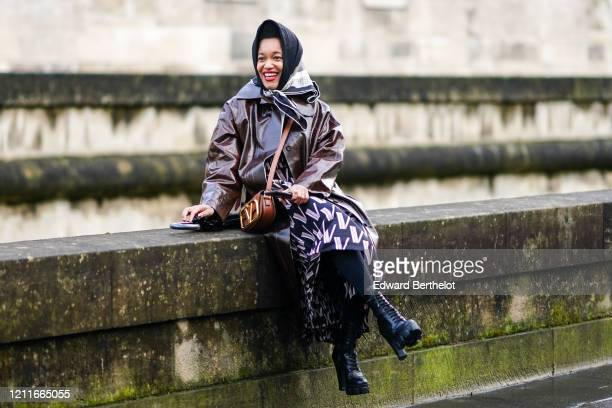 Tamu McPherson wears a scarf over the head, a brown leather long rain coat, a Valentino bag, black leather boots, a Valentino monogram dress, outside...