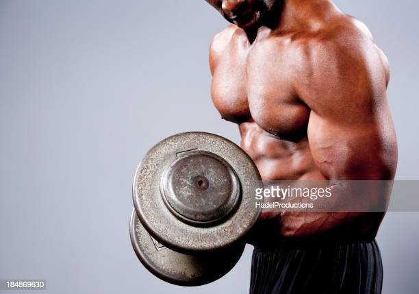 A tan bodybuilder using a heavy barbell