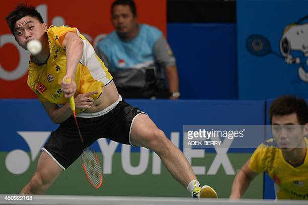 Tan Boon Heong of Malaysia returns a shuttle cock next to Tan Wee Kiong at the 2014 Indonesia Open men double quarter final match against Lee Yong...