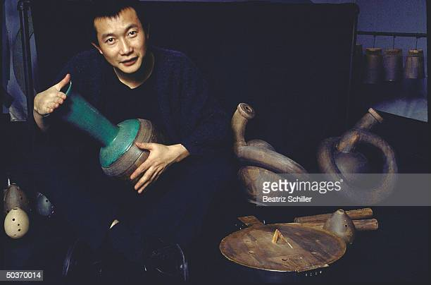 Tan Dun musician conductor composer of the opera Marco Polo for NYC Opera playing an urnshaped percussion instrument amidst various other wind...