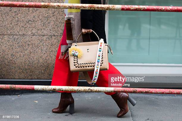 A tan Fendi Fashion Show handbag in white calfskin decorated with metal eyelets and a macroweave is spotted outside the Marco de Vincenzo show during...