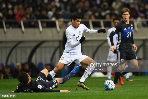 Tanaboon Kesarat of Thailand is tackled by Shinji Kagawa of Japan during the 2018 FIFA World Cup Qualifier match between Japan and Thailand at...