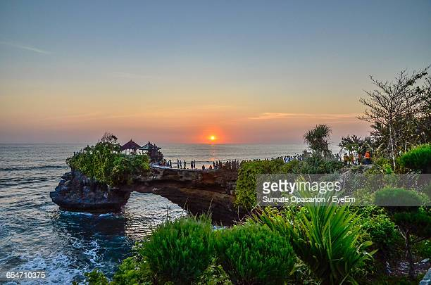 tanah lot by sea against sky during sunset - tanah lot stock pictures, royalty-free photos & images
