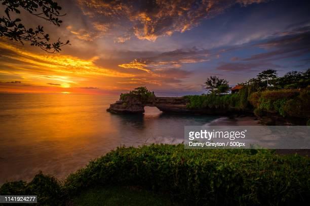 tanah lot sunset - tanah lot stock pictures, royalty-free photos & images