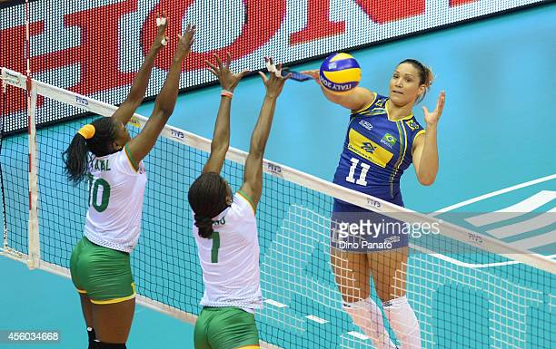Tandara Caixeta of Brazil spikes the ball against to Berthrade Simone Flore Bikatal and Henriette Nadege Koulla of Cameroon during the FIVB Women's...