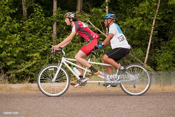 tandem disability racers with pilot in front and blind man - tandem bicycle stock pictures, royalty-free photos & images