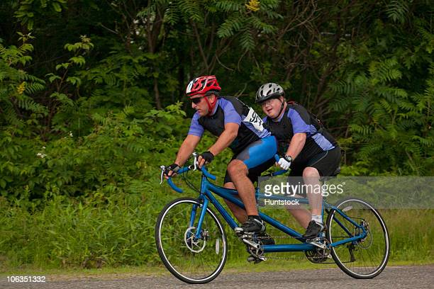 tandem disability racers with pilot in front and man with down syndrome - tree man syndrome stock photos and pictures
