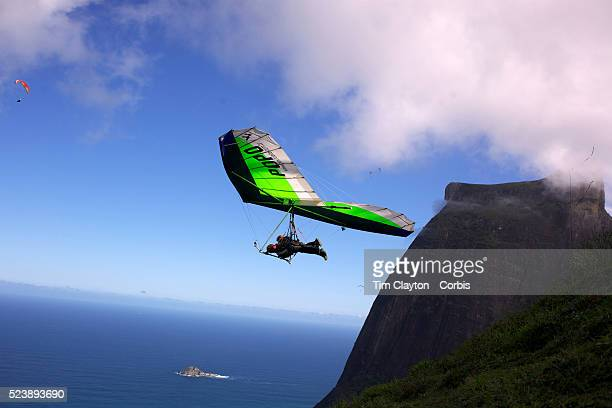 A tandem hang glider flies above the hillside of Pedro Bonita high in the hills of Rio de Janeiro Pilots of hang gliders and para gliders take...