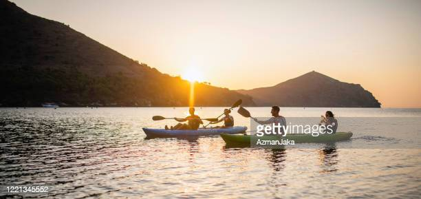 tandem kayakers paddling in mediterranean at sunrise - sea kayaking stock pictures, royalty-free photos & images