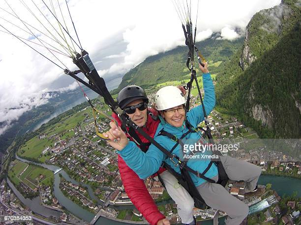 Tandem parasailers descend over city and mountains