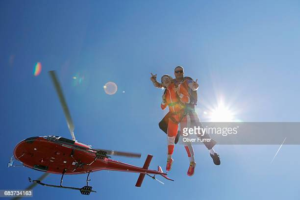 Tandem sky divers free falling with helicopter above, Interlaken, Berne, Switzerland