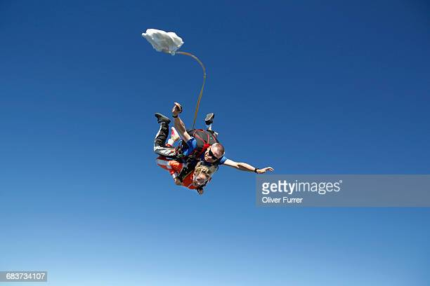 tandem sky divers free falling with parachute opening, interlaken, berne, switzerland - first occurrence stock pictures, royalty-free photos & images