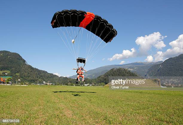 tandem sky divers landing in field with parachute, interlaken, berne, switzerland - landing gear stock photos and pictures