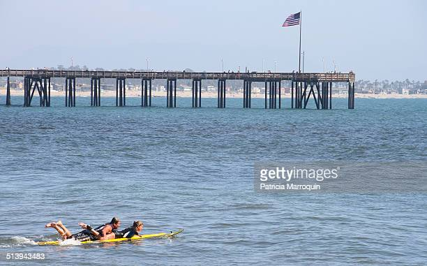 Tandem surfers paddle out near the Ventura Pier in Ventura California USA 2012