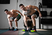 two young man exercising together gym