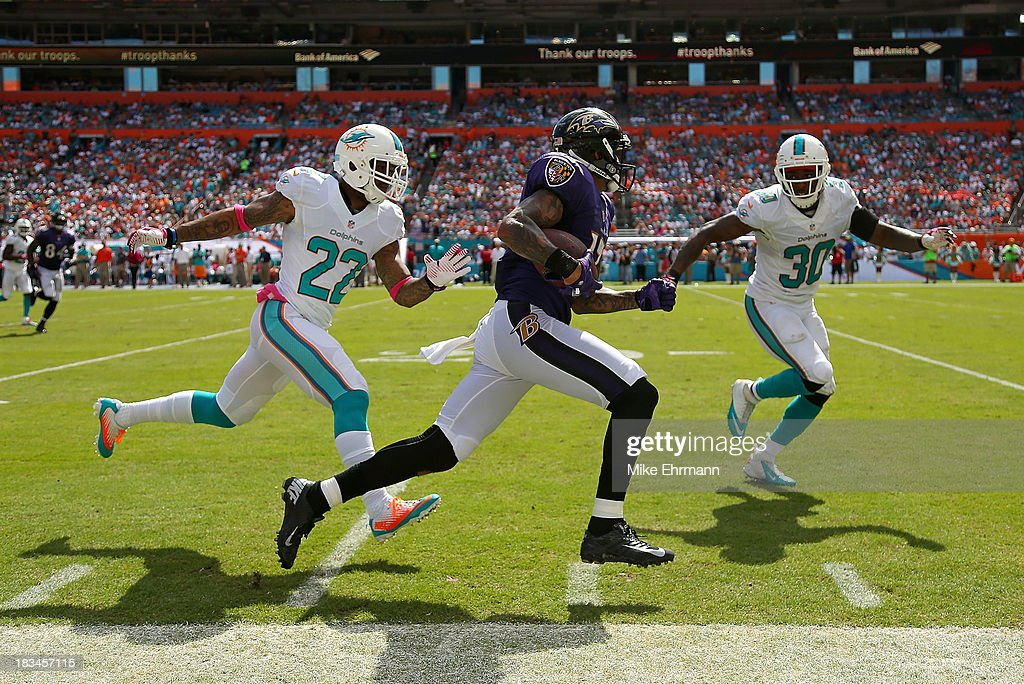Tandon Doss #17 of the Baltimore Ravens runs past Jamar Taylor #22 and Chris Clemons #30 of the Miami Dolphins during a game at Sun Life Stadium on October 6, 2013 in Miami Gardens, Florida.