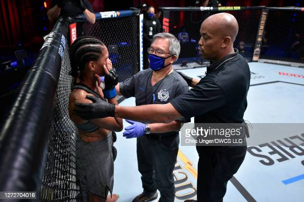 Taneisha Tennant reacts after receiving an inadvertent eye poke from her opponent Danyelle Wolf in their women's featherweight bout during week seven...